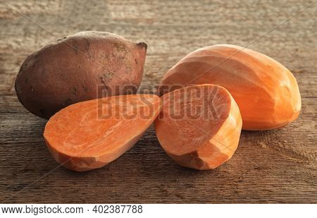 Peeled And Unpeeled Yam Tubers On A Rough Wooden Table. Selective Focus.