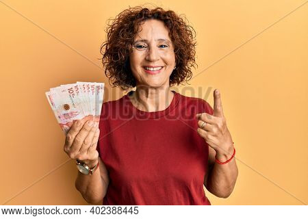 Beautiful middle age mature woman holding 10 colombian pesos banknotes smiling with an idea or question pointing finger with happy face, number one