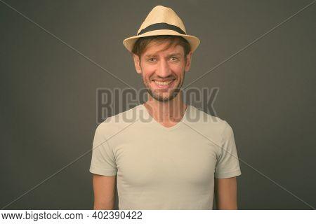 Studio Shot Of Blond Bearded Tourist Man Against Gray Background