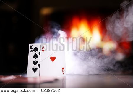 A Pair Of Aces On A Deck Of Playing Cards In A Smoke Against The Background Of A Burning Fireplace.