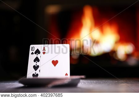 A Pair Of Aces On A Deck Of Poker Cards Against The Background Of A Burning Fireplace. Online Gambli