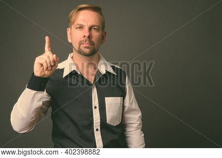 Blond Bearded Businessman With Goatee Against Gray Background
