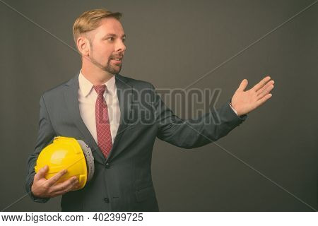 Blond Bearded Businessman With Goatee Holding Hardhat Against Gray Background