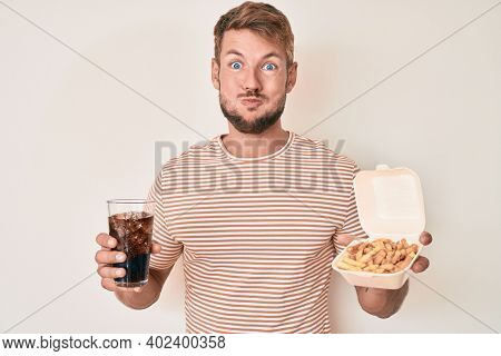 Young caucasian man eating fast food puffing cheeks with funny face. mouth inflated with air, catching air.