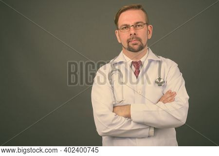 Blond Bearded Man Doctor With Goatee Against Gray Background