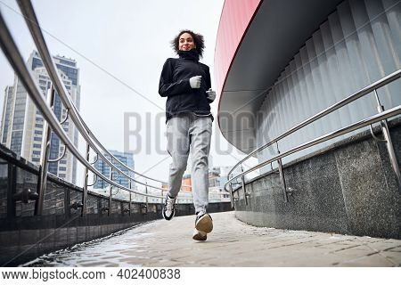 Excited Sportswoman Jogging On An Inclined Road