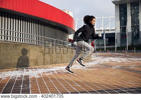 Female Athlete Sprinting Forward On A City Square