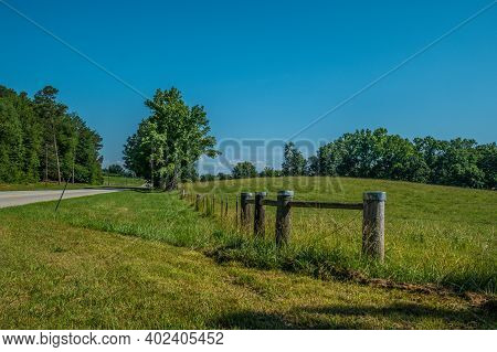 Scenic Drive Down A Rural Country Road With A Rustic Fence With Barbwire Enclosing The Farmland And