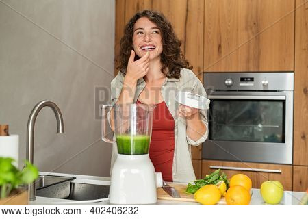 Young woman tasting healthy detox juice made with the blender at home. Fit girl tasting green juice blending with fresh fruits and vegetables in kitchen. Happy smiling girl preparing fruit smoothie.