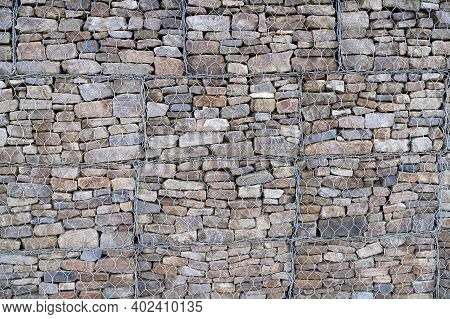 Metal Cage Filled With Rocks Texture . Stone Wall With Metal Grid As Background.  Gabion Net.