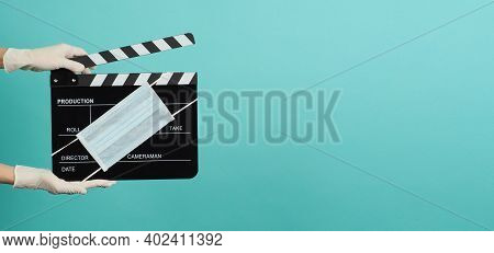 Hand Is Wear White Medical Gloves And Hold Black Clapper Board Or Movie Slate With Face Mask. It Use