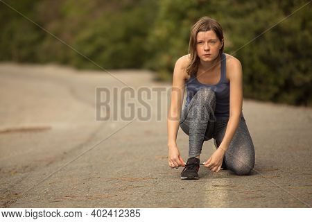 Woman In Sportswear Tying Sneakers Shoelaces On A Road, Preparing To Run A Distance To Train Her Bod