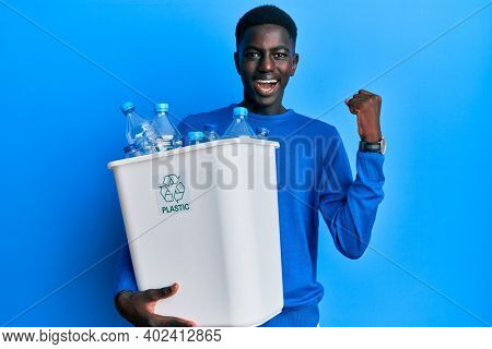 Young african american man holding recycling wastebasket with plastic bottles screaming proud, celebrating victory and success very excited with raised arms