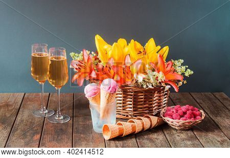 Wicker Basket With Orange And Yellow Lilies And White Hydrangea Flowers, Glasses Of Champagne, Cherr