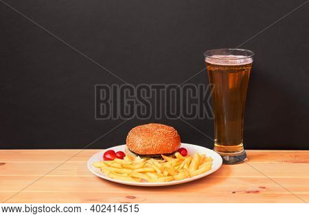 Glass Of Beer, Burger And Fried Potatoes On Wooden Table On Dark Background. View With Copy Space.