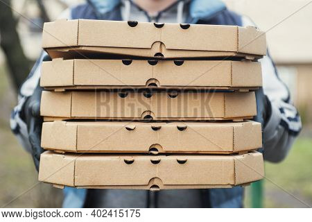 Man Delivering Pizza. A Deliveryman Is Holding A Large Stack Of Pizza Boxes. Pizza Delivery Man Deli