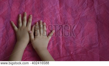 Toddler Hands On Crumpled Tissue Paper On Table. Directly Above View Of Magenta Wrinkled Paper And K