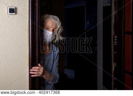 An Older Woman Wearing A Mask Looks Out While Waiting For A Social Worker