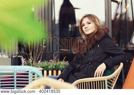 Business Woman In Fox Fir Dawn Jacket With Hood Close Up Photo On City Open Air Cafe Background
