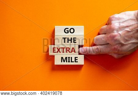 Go The Extra Mile Symbol. Wooden Blocks With Words 'go The Extra Mile'. Male Hand. Beautiful Orange