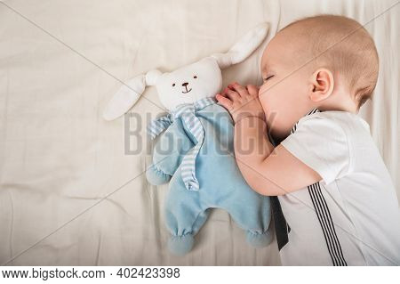Newborn Toddler With A Toy On The Bed Close-up And Copy Space. The Child Sleeps On A Large Bed In Th