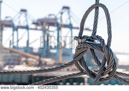 Twisted Wire Rope Knot Closeup With Blurred Industrial Landscape Of Port Pier On Background. Tis Car