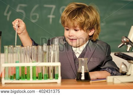 Little Kid Learning Chemistry In School Laboratory. Little Boy At Chemical Cabinet. Kid In Lab Coat
