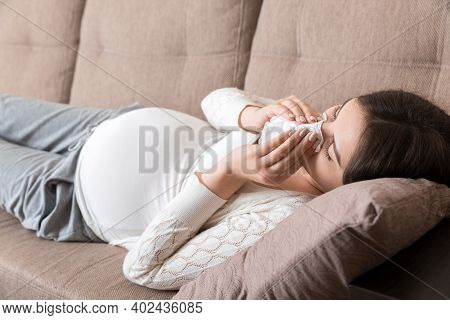 Sick Pregnant Woman Blowing Nose Into Tissue At Home Healthy Millennial Healthcare Concept