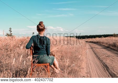 A Barefoot Caucasian Woman Dressed In Casual Clothes Sits In A Field Near A Country Road. The Lady I
