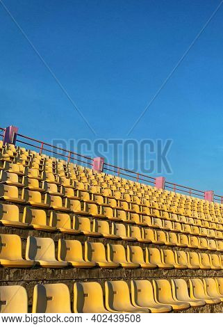 Empty Yellow Color Football (soccer) Stadium Seats In The Summer  - Sunny   Day With Clear Blue Sky
