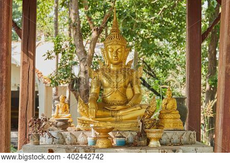 Phayao, Thailand - Dec 6, 2020: Gold God Statue In Pavilion On Green Forest Background In Wat Analay