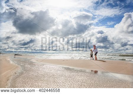 Brothers walking on the beach on a cloudy windy day