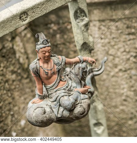stone statue of bodhisattva sit on a cloud in a garden