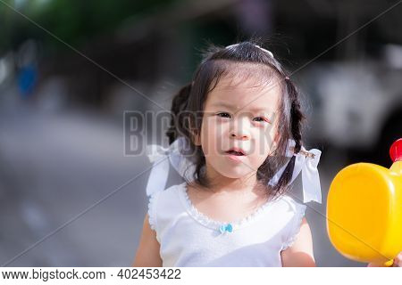 Portrait Happy Asian Little Child Girl Standing In Front Of House. In Her Hand Holding Yellow Wateri