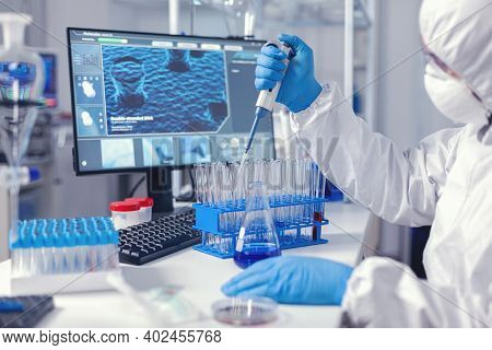 Medic Assistant Working In Biochemistry Lab Working With Automatic Pipette Wearing Protection Suit.