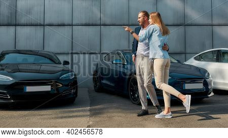 Young Caucasian Couple Choosing New Car For Buying While Walking Along Row Of Autos Outdoors, Widesc