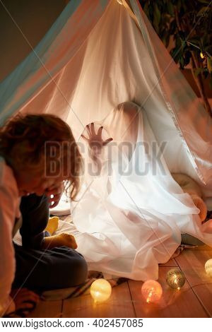 Two Siblings, Boy And Girl Playing Together At Home. Little Girl Playing Ghost While Sitting In A Hu
