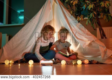 Two Little Children, Brother And Sister Reading Stories Together While Sitting On A Blanket In A Tee