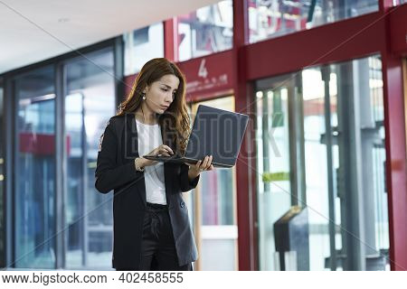 Asian Businesswoman Checking Email Using Laptop Computer While Walking In Company Lobby