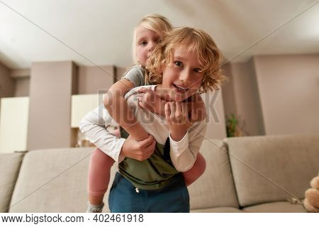 Cute Little Siblings, Boy And Girl Smiling At Camera While Playing Together At Home. Siblings Relati