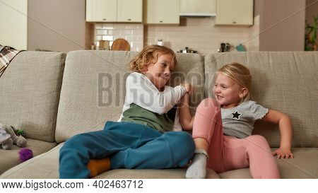Portrait Of Happy Little Children, Boy And Girl Playing Together, Having Arm Wrestling Competition O
