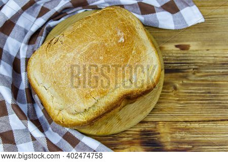 Homemade Loaf Of Bread On A Wooden Table Freshly Baked In An Electric Bread Maker. Homemade Baking