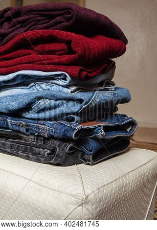 Basic Wardrobe, Clothes Wardrobe. One-on-one Folded Jeans And Blouses In Burgundy Colors On An Ottom
