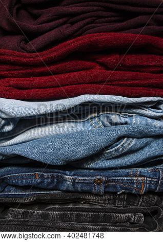 A Basic Wardrobe, Clothes Wardrobe. One-on-one Folded Jeans And Blouses In Burgundy Colors Close-up,