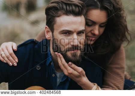 Portrait Of Two Caucasian Lovers. Young Couple Is Hugging On Autumn Day Outdoors. A Bearded Man And