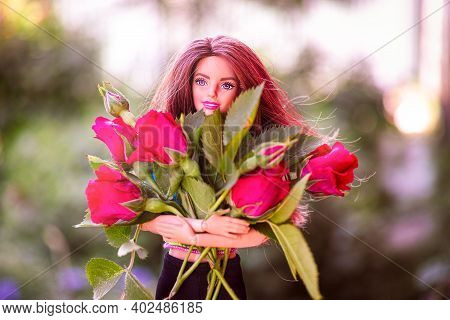 Tambov, Russian Federation - June 12, 2020 Brunette Barbie Doll With Bouquet Of Red Roses Outdoors.