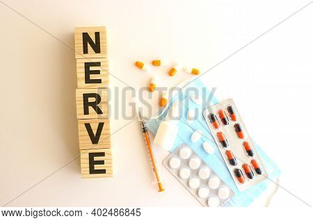 The Word Nerve Is Made Of Wooden Cubes On A White Background With Medical Drugs And Medical Mask.