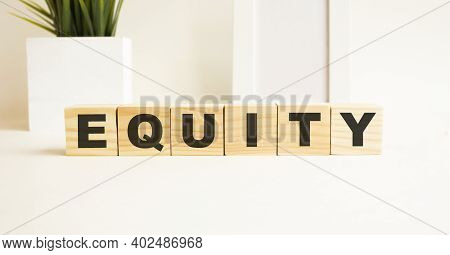 Wooden Cubes With Letters On A White Table. The Word Is Equity. White Background With Photo Frame, H