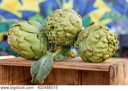 Fresh Green Mediterranean Artichokes On The Wooden Box For Sale One Holiday At The Market.
