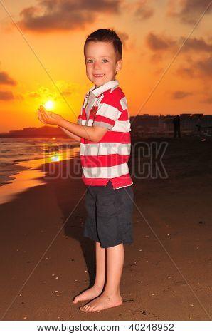 Little boy holding sun on sunset.